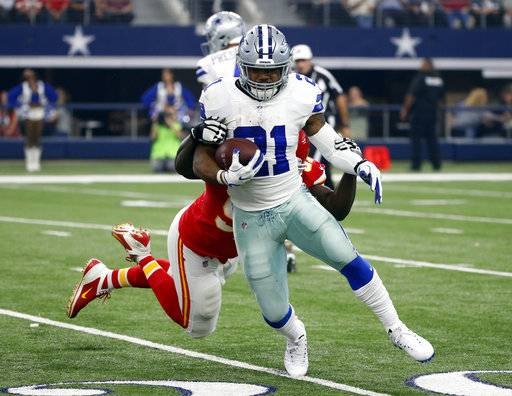 Dallas Cowboys running back Ezekiel Elliott (21) carries the ball as Kansas City Chiefs defensive end Allen Bailey, rear, attempts the stop in the first half of an NFL football game, Sunday, Nov. 5, 2017, in Arlington, Texas.