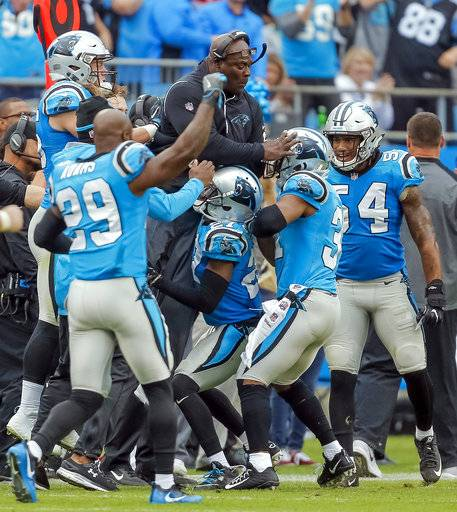 FILE - In this Sunday, Nov. 5, 2017, file photo, the Carolina Panthers defense celebrate by lifting assistant defensive backs/safeties coach Richard Rodgers along the sidelines after they stopped the Atlanta Falcons on fourth down in the second half of an NFL football game in Charlotte, N.C. The Panthers have always been a strong defense under Ron Rivera, but they're back to be being No. 1 behind the help of some veteran players.