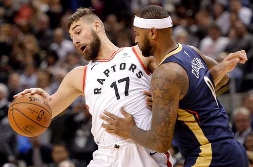 Toronto Raptors center Jonas Valanciunas (17) gets blocked on a drive to the net by New Orleans Pelicans center DeMarcus Cousins (0) during the first half of an NBA basketball game Thursday, Nov. 9, 2017, in Toronto. (Nathan Denette/The Canadian Press via AP)