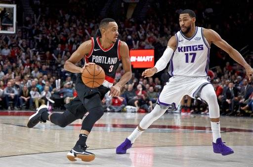 Portland Trail Blazers guard CJ McCollum, left, dribbles past Sacramento Kings guard Garrett Temple during the second half of an NBA basketball game in Portland, Ore., Saturday, Nov. 18, 2017.