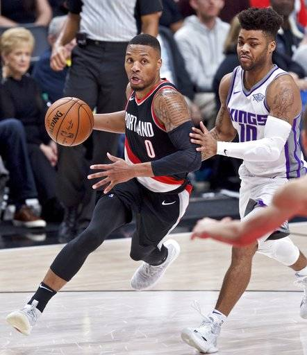 Portland Trail Blazers guard Damian Lillard, left, dribbles past Sacramento Kings guard Frank Mason III during the second half of an NBA basketball game in Portland, Ore., Saturday, Nov. 18, 2017.