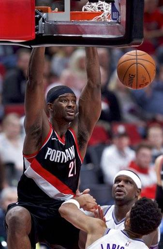 Portland Trail Blazers forward Noah Vonleh, left, dunks over Sacramento Kings forward Zach Randolph, rear, and forward Skal Labissiere during the second half of an NBA basketball game in Portland, Ore., Saturday, Nov. 18, 2017.