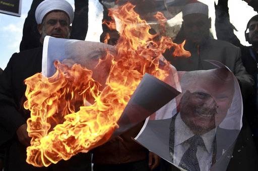 Palestinians burn posters of Israeli Prime Minister Benjamin Netanyahu and U.S. President Donald Trump, during a protest against the U.S. decision to recognize Jerusalem as Israel's capital, in Gaza City Thursday, Dec. 7, 2017.