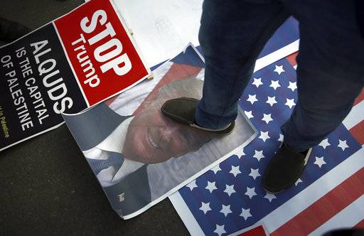A Palestinian steps on a poster of U.S. President Donald Trump and a representation of the American flag during a protest against the U.S. decision to recognize Jerusalem as Israel's capital, in Gaza City Thursday, Dec. 7, 2017.