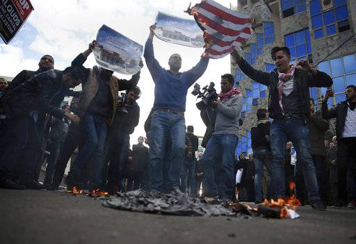 Palestinian protesters chant angry slogans as one burns a representation of the American flag, during a protest against the U.S. decision to recognize Jerusalem as Israel's capital, in Gaza City Thursday, Dec. 7, 2017.