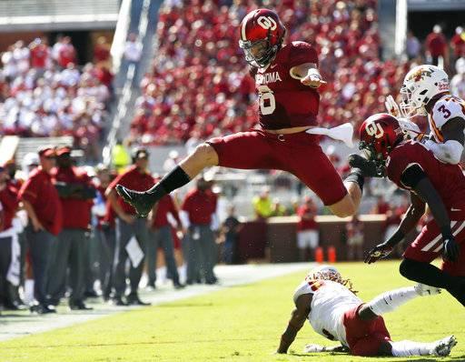 FILE - In this Oct. 7, 2017, file photo, Oklahoma quarterback Baker Mayfield (6) leaps over Iowa State defensive back De'Monte Ruth, bottom, in the second quarter of an NCAA college football game in Norman, Okla. Baker Mayfield is the AP player of the year, becoming the fourth Oklahoma quarterback to win the award since it was established in 1998.