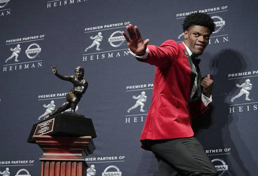 FILE - In this Saturday, Dec. 10, 2016, file photo, Louisville's Lamar Jackson poses with the Heisman Trophy after winning the award, in New York.  If anything, Heisman Trophy winner Lamar Jackson has been better this season than last. He has passed for 3,489 yards, ran for 1,443 yards and accounted for 42 touchdowns - another jaw-dropping performance for a Louisville team that was good, but not great. He believed he did enough to be a Heisman finalist and he got his wish.