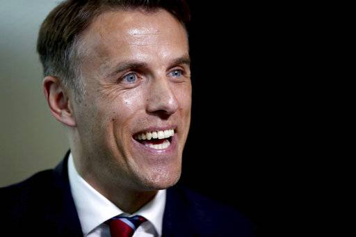 Newly appointed head coach for the England women's soccer team, Phil Neville speaks to the media during his official unveiling at St George's Park, in Burton, England, Monday, Jan. 29, 2018. (Nick Potts/PA via AP)