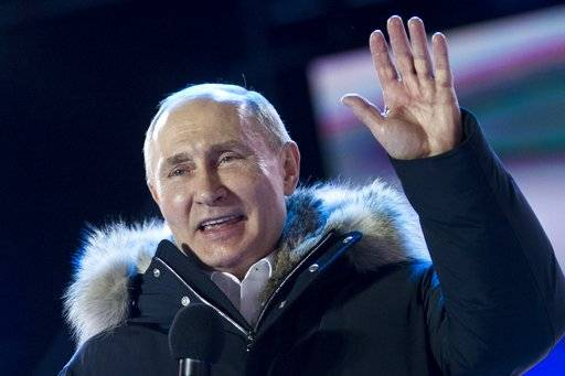 Russian President Vladimir Putin waves after speaking to supporters during a rally near the Kremlin in Moscow, Sunday, March 18, 2018. Vladimir Putin headed to an overwhelming win in Russia's presidential election Sunday, adding six years in the Kremlin for the man who has led the world's largest country for all of the 21st century.