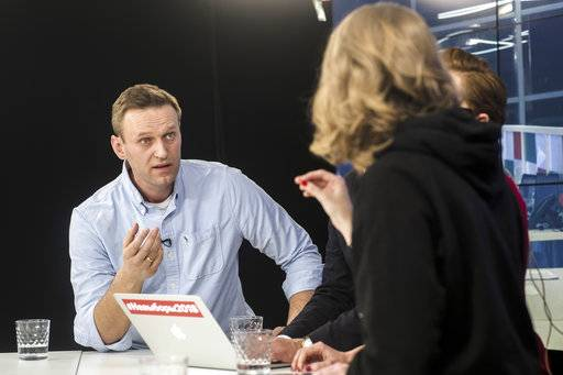 Russian opposition leader Alexei Navalny, left, speaks with Presidential candidate Ksenia Sobchak, back to a camera, as they observe election progress at the Foundation for Fighting Corruption office, in Moscow, Russia, Sunday, March 18, 2018. An exit poll suggests that Vladimir Putin has handily won a fourth term as Russia's president, adding six more years in the Kremlin for the man who has led the world's largest country for all of the 21st century. (Evgeny Feldman/Navalny Campaign via AP)
