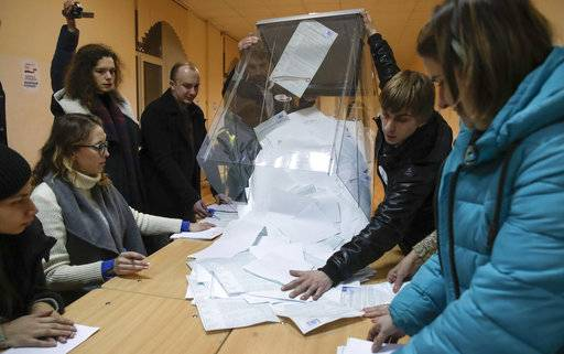 The members of the local election commission open a ballot box for counting at a polling station, during the presidential elections in St.Petersburg, Russia, Sunday, March 18, 2018. Russians are voting in a presidential election in which Vladimir Putin is seeking a fourth term in the Kremlin.