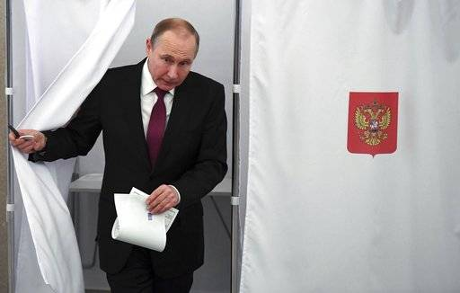 Russian President and Presidential candidate Vladimir Putin exits a polling booth as he prepares to cast his ballot during Russia's presidential election in Moscow, Russia, Sunday, March 18, 2018. Putin's victory in Russia's presidential election Sunday isn't in doubt. The only real question is whether voters will turn out in big enough numbers to hand him a convincing mandate for his fourth term - and many Russian workers are facing intense pressure to do so. (Yuri Kadobnov/Pool Photo via AP)