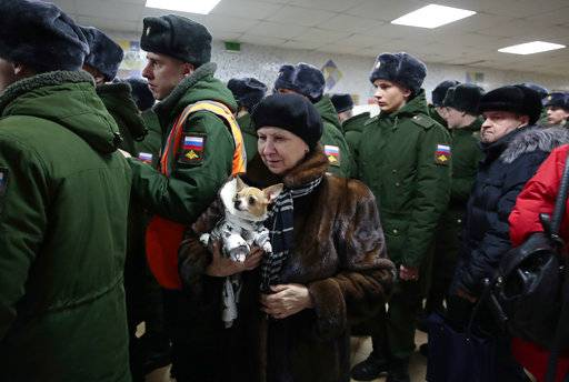 A woman with her dog lines up with Russian military personnel to vote in the presidential election in Moscow, Russia, Sunday, March 18, 2018. Russians are voting in a presidential election in which Vladimir Putin is seeking a fourth term in the Kremlin.