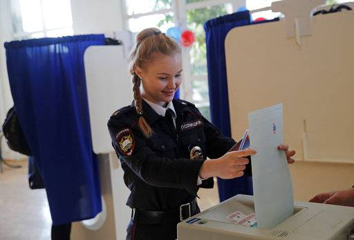 A police cadet casts her vote in the presidential election in Moscow, Russia, Sunday, March 18, 2018. Russians are voting in a presidential election in which Vladimir Putin is seeking a fourth term in the Kremlin.