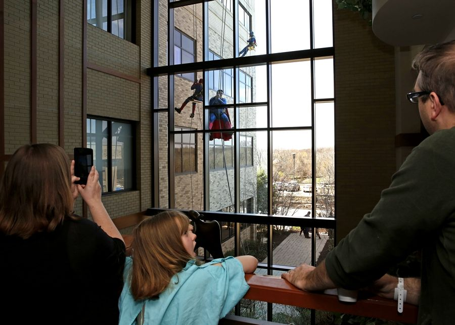Wheaton parents Megan and Jeremy Kunkel and their 8-year-old daughter, Teagan, watch window washers dressed as Spider-Man, Superman and Captain America scale the exterior of the Northwestern Medicine Central DuPage Hospital Women's and Children's pavilion Monday.