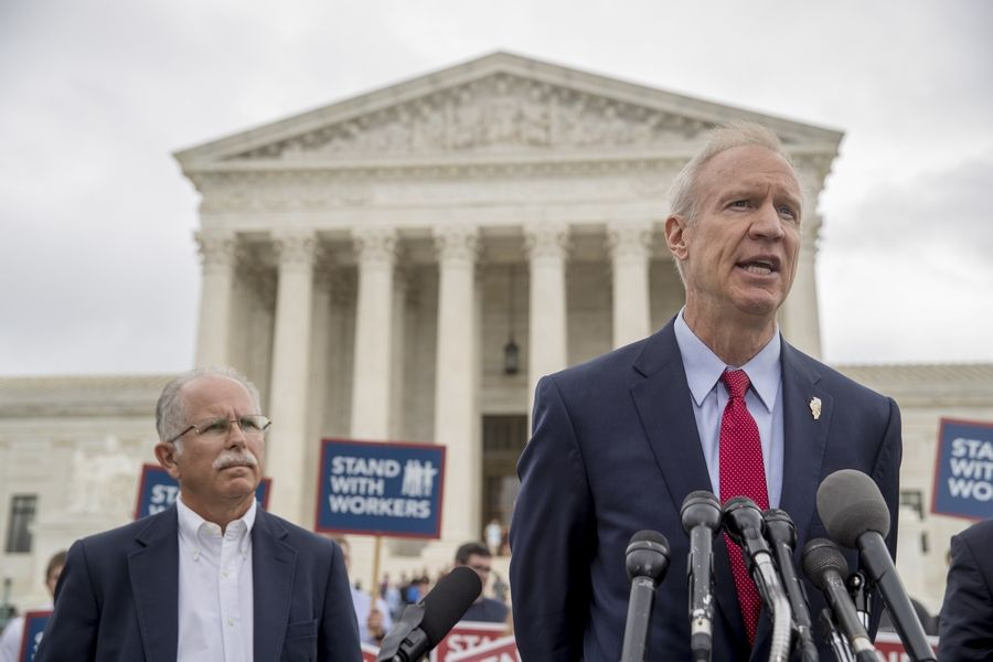 Gov. Bruce Rauner, right, accompanied by plaintiff Mark Janus, left, speaks outside the Supreme Court in Washington Wednesday after the court rules in a setback for organized labor that states can't force government workers to pay union fees.