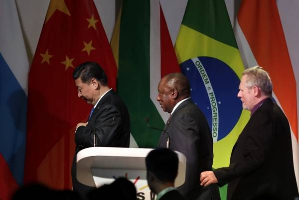 China's President Xi Jinping, left, with South African President Cyril Ramaphosa, middle, and Robert Haydn Davies, minister of trade and industry of South Africa, leave the stage after the opening of the BRICS Summit in Johannesburg, South Africa, Wednesday, July 25, 2018. The summit runs through Friday with various heads of BRICS attending.