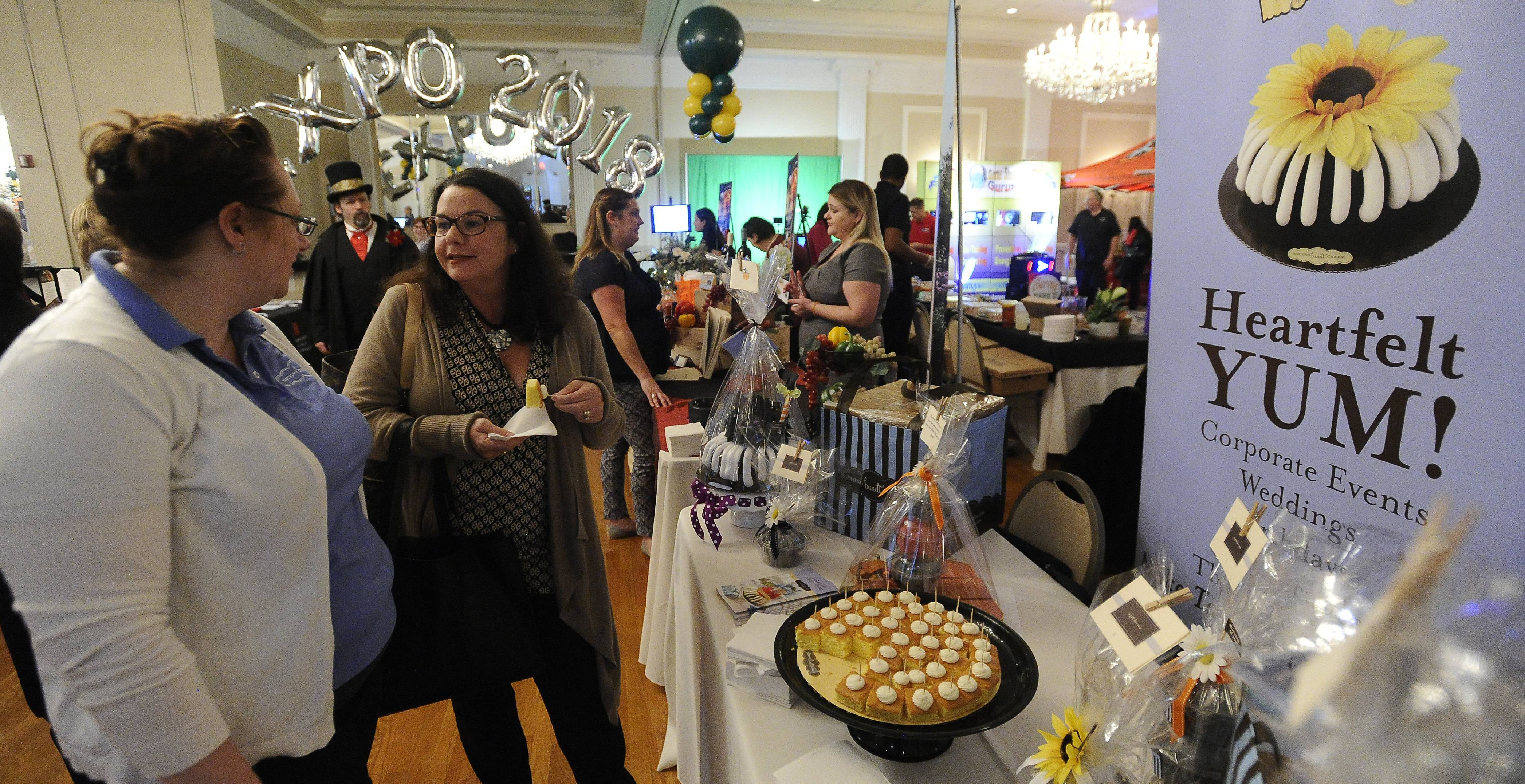 Jessica Aviles of Nothing Bundt Cakes talks with Susan Rose of Western Springs at the Daily Herald Business Ledger's DuPage Hospitality Expo.