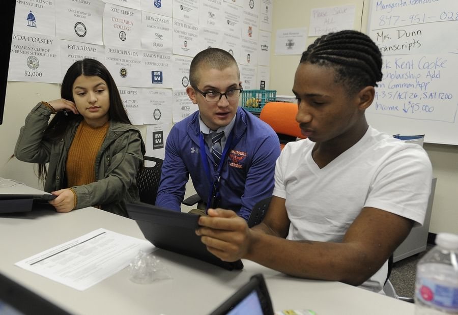 Mykel Brewer, 17, works with AP science teacher Logan Nelson as Cassandra Sanchez, 17, looks on while they cover material from the class at Hoffman Estates High School. Providing opportunities to earn college credit through Advanced Placement classes is one way high schools help students' college and career readiness.