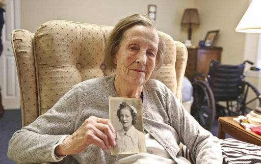 In this Nov. 1, 2018 photo, Lorriane Baer, 99, holds a photo of herself and talks about her time as a Army nurse in WWII at her home in Decatur, Ill. During World War II, it was every American's patriotic duty to serve the war effort in some way.For many of the men, that was putting on a uniform and going to fight. For a lot of women, it  meant joining the women's branches of each armed service, which were separate then. H. Lorraine Eades, as she was known then, was finishing up nursing school at John C. Proctor Hospital in Peoria when an Army recruiter came to visit and asked the students if they would serve. On Veterans Day 2018, she and the women in that class represent a critical component of the war effort. (Clay Jackson/Herald & Review via AP)/