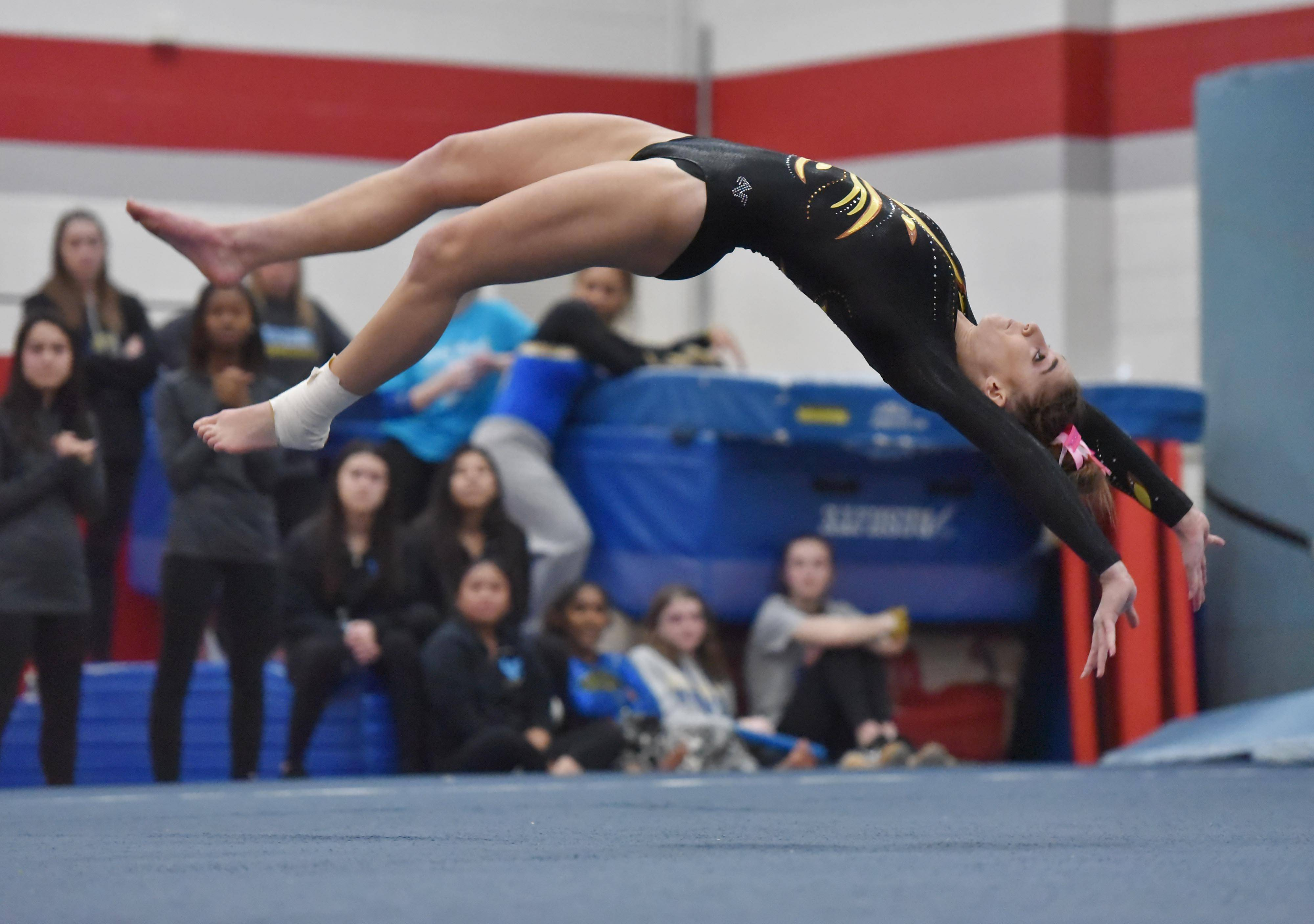 Carmel's Izzy Kropiwiec flips through her Floor Exercise routine at the Lake County girls gymnastics meet Saturday at Mundelein High School.