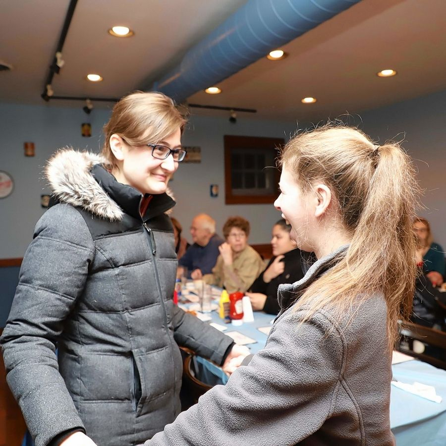 Friend Lindsey Wettle, left, greets Jenny Callen at her fundraiser. The event raised $400 to help cure Williams Syndrome.
