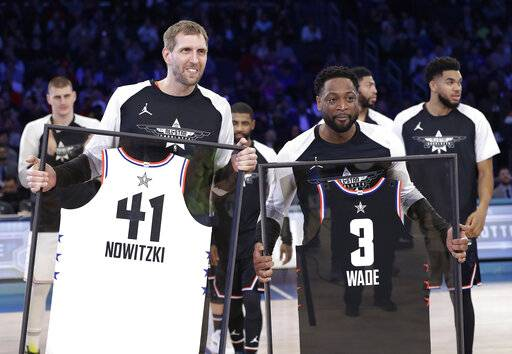 CORRECTS TO DWYANE, NOT SWAYNE - Team Giannis' Dirk Nowitzki, of the Dallas Mavericks, and Team LeBron's Dwyane Wade, of the Miami Heat, are given jerseys during the second half of an NBA All-Star basketball game, Sunday, Feb. 17, 2019, in Charlotte, N.C. The Team LeBron won 178-164.