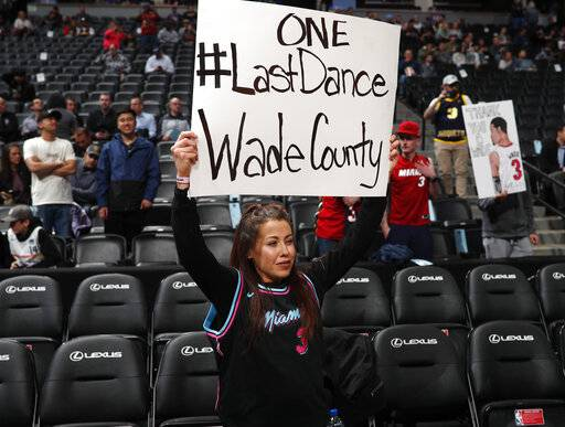 A Miami Heat fan holds up a sign for Heat guard Dwyane Wade in the first half of an NBA basketball game against the Denver Nuggets Monday, Feb. 11, 2019, in Denver.