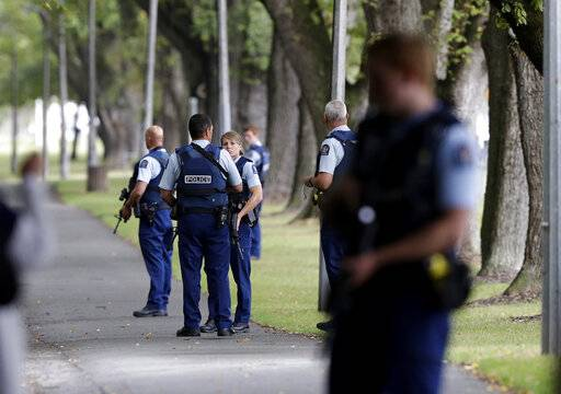 Police keep watch at a park across the road from a a mosque in central Christchurch, New Zealand, Friday, March 15, 2019.  Multiple people were killed in mass shootings at two mosques full of people attending Friday prayers, as New Zealand police warned people to stay indoors as they tried to determine if more than one gunman was involved.