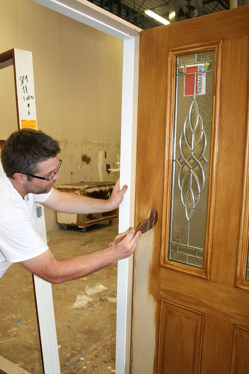 A worker stains a new door in preparation for its installation.