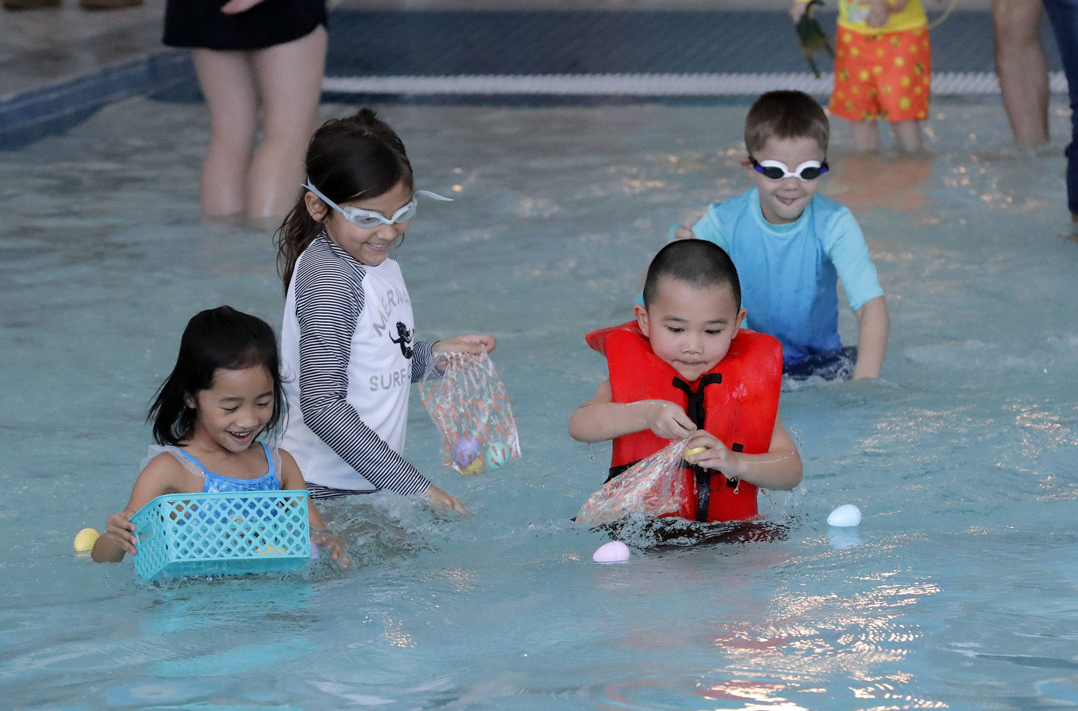 Kids dash for eggs as kids put on their swimsuits and goggles for an Aqua Egg Hunt at the Club at Prairie Stone in Hoffman Estates Saturday.