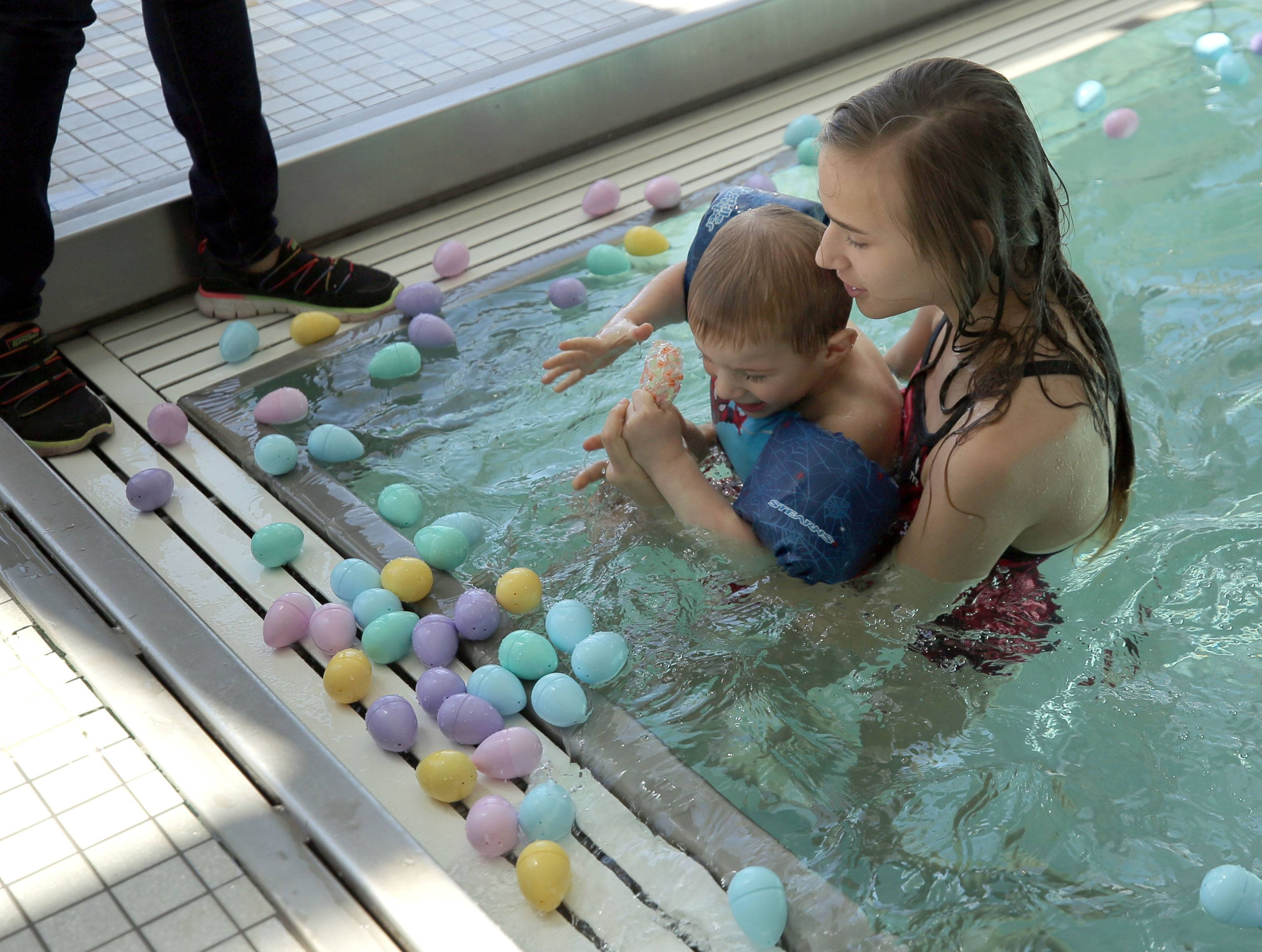 Maya Kieltyka, 12, of Hoffman Estates and her 3-year-old brother Alexander try to scoop up eggs as kids put on their swimsuits and goggles for an Aqua Egg Hunt at the Club at Prairie Stone in Hoffman Estates Saturday.