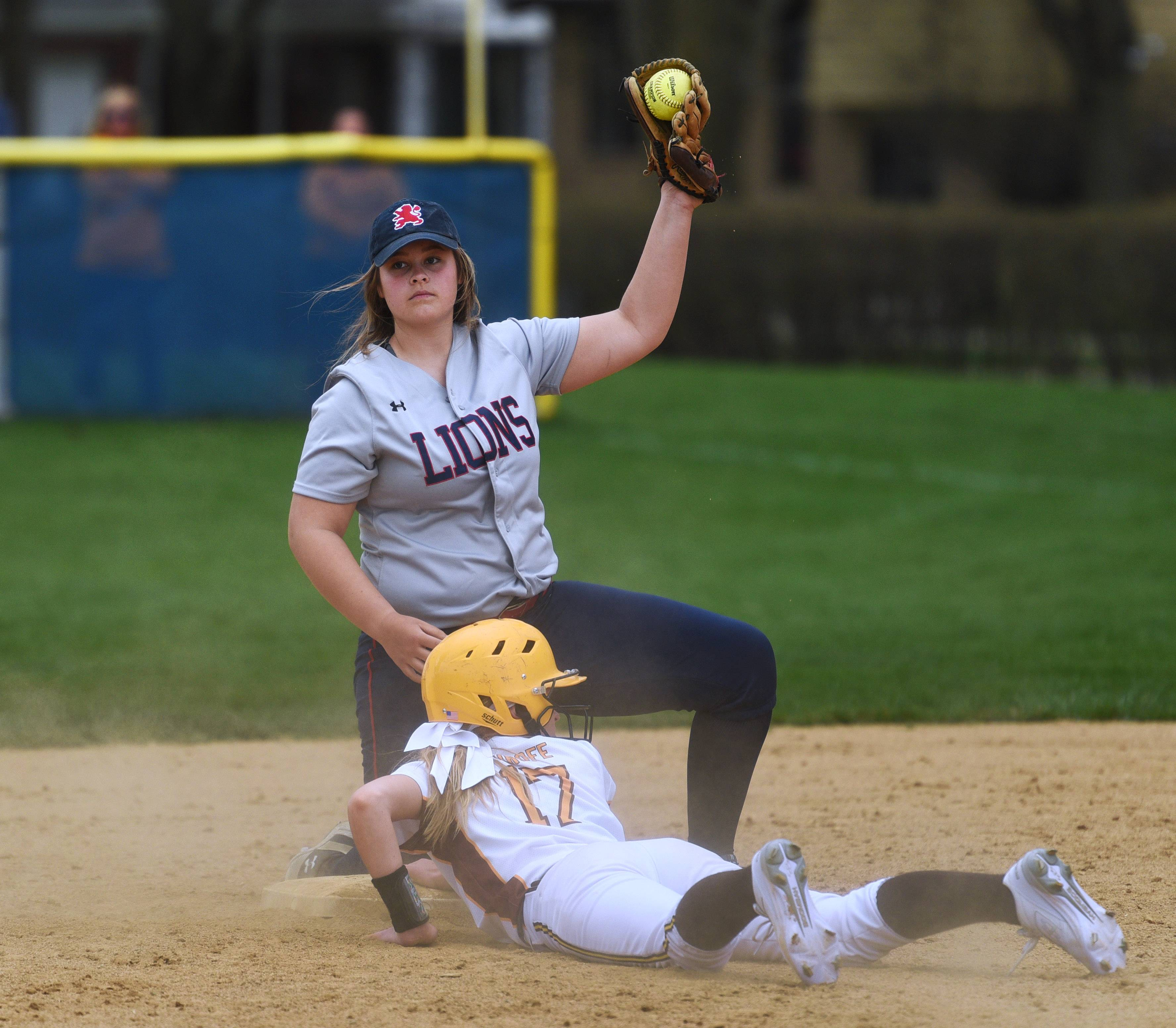 St. Viator's CeCe Kaiser shows the umpired the ball after tagging out Carmel's Caiti Shrofe at second base during Monday's softball game in Arlington Heights.