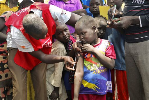 In this photo taken Wednesday, April 17, 2019, a community health worker vaccinates children against measles outside of Kuajok, South Sudan. As South Sudan emerges from a five-year civil war it is grappling with a measles outbreak in which more than 750 cases, including seven deaths, have been reported since January - almost six times the number of cases for all of 2018, according to WHO data.