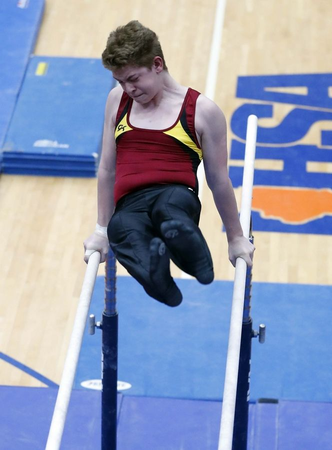 Nathan Frank of Schaumburg High School on the parallel bars Saturday during the State boys gymnastics meet at Hoffman Estates High School.