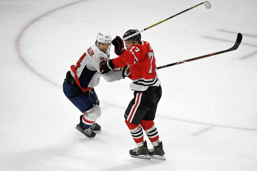 Chicago Blackhawks' Kirby Dach (77) battles Washington Capitals' Jonas Siegenthler (34) of Denmark, for position during the third period of an NHL hockey game Sunday, Oct. 20, 2019, in Chicago. Chicago won 5-3.