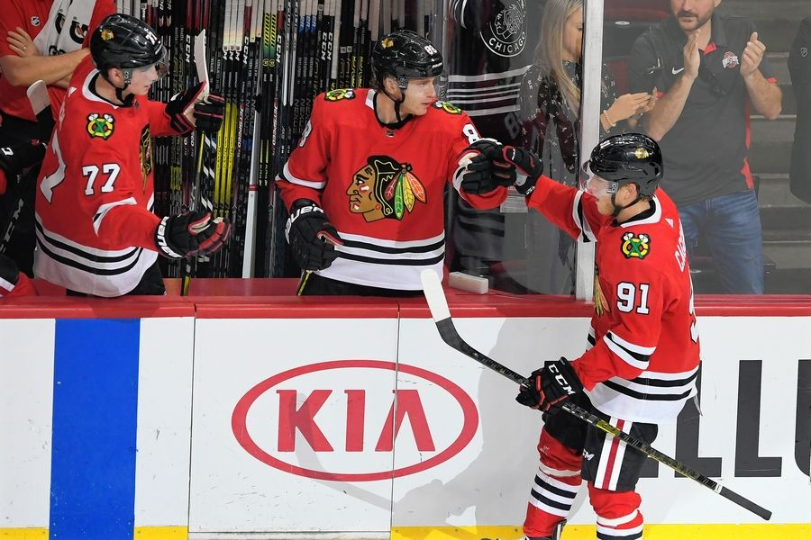 The Blackhawks' Drake Caggiula (91) celebrates with teammates Patrick Kane (88) and Kirby Dach (77) on the bench after scoring a goal Sunday against the Washington Capitals in Chicago.