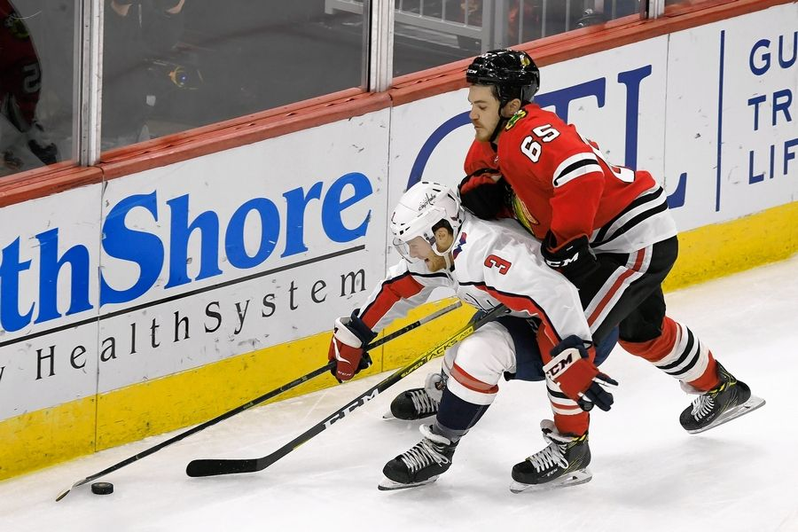 Chicago Blackhawks' Andrew Shaw (65) battles Washington Capitals' Nick Jensen (3) for control of the puck during the first period of an NHL hockey game Sunday, Oct. 20, 2019, in Chicago. Chicago lost 5-3.