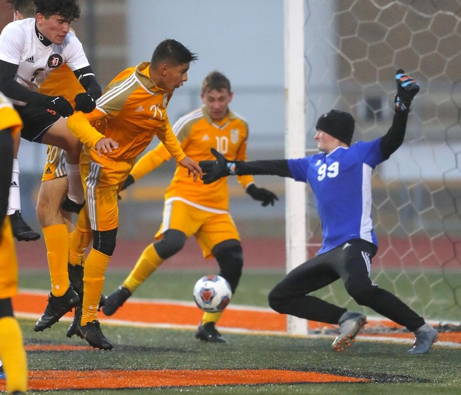 Jacobs' Ruben Zarate, left, lands after heading the ball while teammate Christopher Loizzi prepares to chip the ball in the goal for their third goal against DeKalb in a 7-2 win Wednesday at the Class 3A DeKalb sectional.