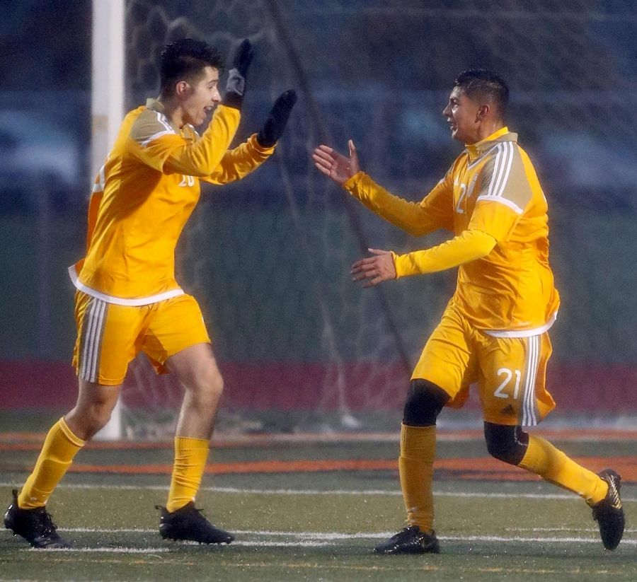 Jacobs' Bryan Ramos-Munoz, left, celebrates with Ruben Zarate after Jacobs' fifth goal against DeKalb in boys sectional soccer action at DeKalb Wednesday night.