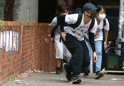 People wearing face masks duck down as they walk at Hong Kong Polytechnic University in Hong Kong, Tuesday, Nov. 19, 2019. About 100 anti-government protesters remained holed up at a Hong Kong university Tuesday as a police siege of the campus entered its third day.