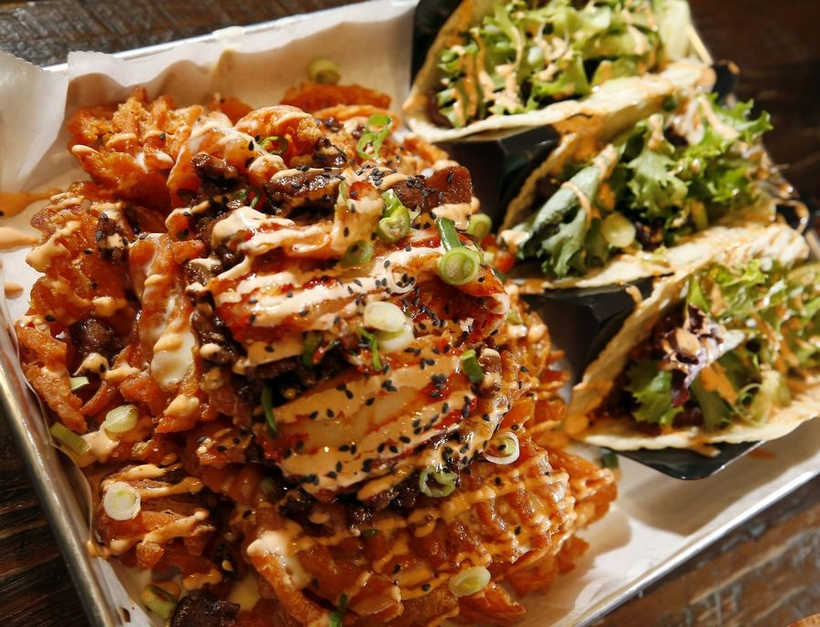 Gogi and waffles, left, starts with sweet potato waffle fries, while tacos feature Korean flavors at Seoul Taco, which opened Friday at 206 S. Washington St. in downtown Naperville.