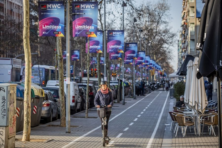 An electric scooter rider travels down a bicycle lane alongside advertising banners for the now-cancelled Mobile World Congress event close to Plaza Espana in Barcelona, Spain, on Feb. 13, 2020.