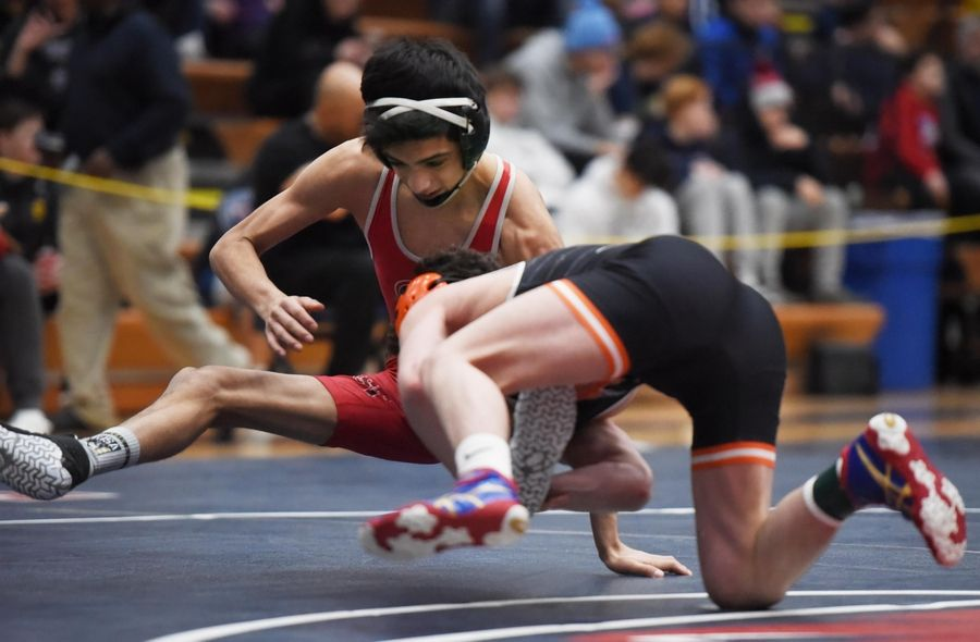DeKalb's Ben Aranda throws Glenbard East's Miguel Garcia in their 106-pound championship bout at the Conant wrestling sectional meet Saturday in Hoffman Estates.