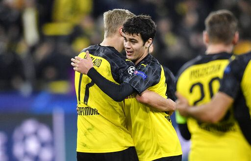 Dortmund's Giovanni Reyna, right, embraces Dortmund's Erling Braut Haaland after the Champions League round of 16 first leg soccer match between Borussia Dortmund and Paris Saint Germain in Dortmund, Germany, Tuesday, Feb. 18, 2020. Reyna is the youngest American ever playing in Champions League.
