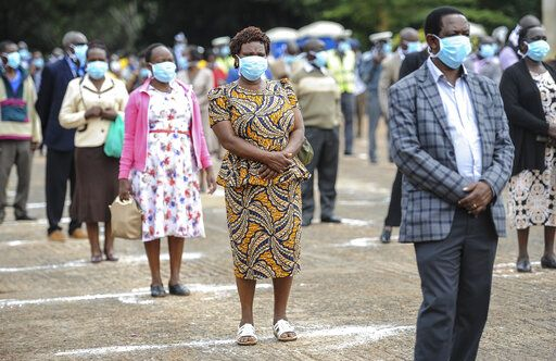 County workers practise social distancing and wear masks as they queue to renew their employment contracts in Uhuru Park in downtown Nairobi, Kenya Monday, April 6, 2020. Kenya on Monday increased its restrictions to combat the new coronavirus, announcing travel bans into and out of the capital city, Nairobi, the port of Mombasa and two counties.