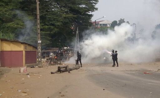 In this image made from video, security forces fire tear gas after a group of local residents demonstrated outside a coronavirus medical reception facility that was under construction in the Yopougon area of the commercial capital Abidjan, Ivory Coast, Monday, April 6, 2020. The protesters hampered the government's effort to build the emergency coronavirus medical reception facility in the crowded Yopougon area, ransacking the site and destroying equipment to be used to construct the center, saying they are worried that the triage center could expose their community to COVID-19.