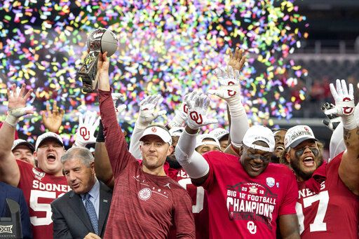 FILE - In this Dec. 7, 2019, file photo, Oklahoma head coach Lincoln Riley hosts the Big 12 Conference championship trophy after defeating Baylor 30-23 in overtime in an NCAA college football game in Arlington, Texas. Riley will earn an average of more than $7.5 million a year under a contract extension through the 2025 season. The university's board of regents approved the two-year extension Tuesday, July 28, 2020.