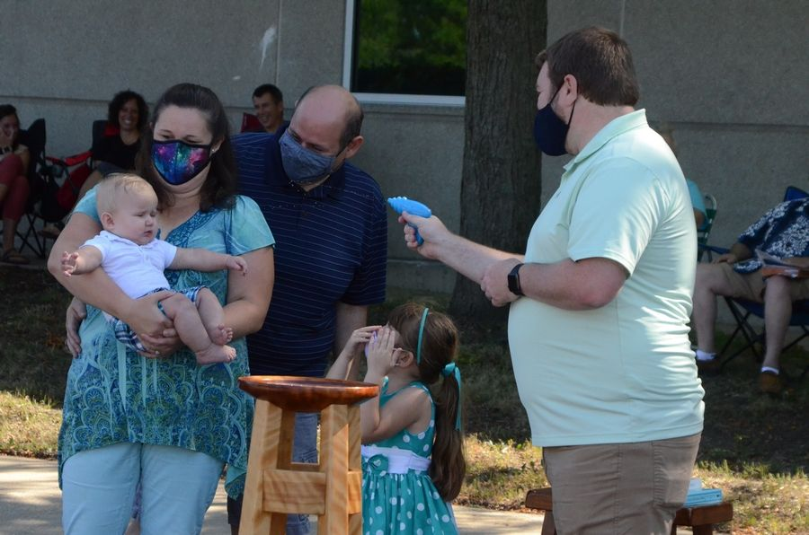 Jackson Walters of North Aurora, left, is baptized with a water gun Sunday, Aug. 16, by Rev. Derek Rogers, pastor at Aurora's Flowing Forth United Methodist Church. From left are Ivy Walters, Jarrod Walters and sister Noelle Walters.