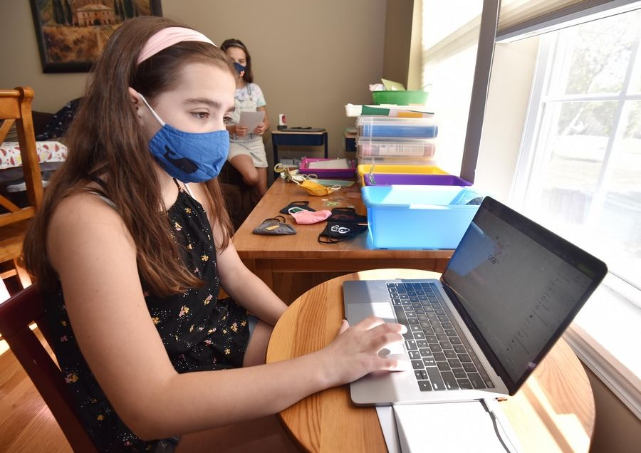 Olivia Bartusch works on a computerized design while her sister, Jaina, waits to print the design into a patch that'll be ironed onto a mask.